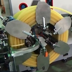 Hose coiling and strapping machine